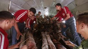 Soldiers and volunteers load wood on an Indian Air Force helicopter to be used for mass cremation at Kedarnath