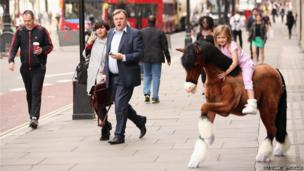Shadow Chancellor of the Exchequer Ed Balls walks past five year old Lottie riding a Clydesdale Prancing Pony outside Hamleys toy shop in London