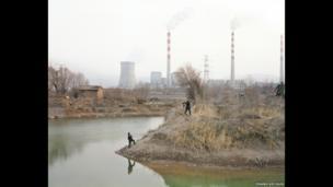 Two people taking pictures by the river in Gansu province