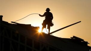 Construction worker carries out work at dawn in Queen Creek, Arizona (27 June 2013)