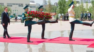 British Prime Minister David Cameron (left) arrives ahead of a wreath-laying ceremony at the Monument of the Motherland Defenders in Astana, Kazakhstan