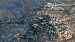 An aerial view of a strip of fire retardant that kept a large part of Yarnell, Arizona, free from fire.