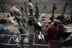 Members of the press mark their spots on the pavement as they set up outside the the Lindo Wing of St Mary's Hospital