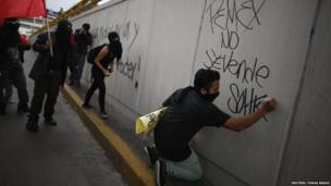 A demonstrator writes graffiti, which reads