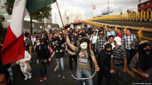 A masked demonstrator holds up a Mexican flag during a march to protest against an alleged government plan to privatize Pemex, 1 July
