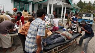 Earthquake victims receive medical treatment outside a community health centre in Bener Meriah, Aceh province, Indonesia, 2 July 2013