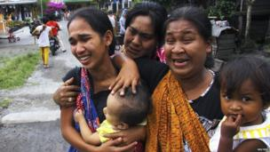 Women carrying children cry outside their homes after a 6.1 magnitude earthquake hit in Bener Meriah district in Central Aceh, Indonesia, 2 July 2013