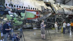 Television crews film the partially reconstructed shell of the remains of TWA Flight 800