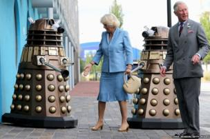 Prince Charles and the Duchess of Cornwall pose next to two Daleks