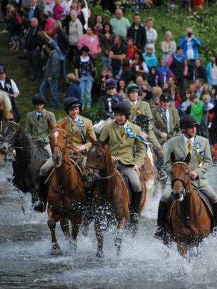 People on horseback cross the River Tweed