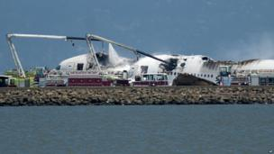 A fire engine sprays water on Asiana Flight 214 after it crashed at San Francisco International Airport on Saturday