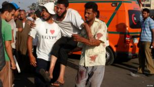 Pro-Morsi supporters help a wounded man outside the Presidential Guards' Club in Cairo on 8 July 2013