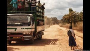 A truck passes Tanzanian schoolgirl Sylvia on a main road