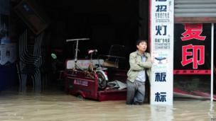 This picture taken on 9 July 2013 shows a man standing in his flooded shop in a district in Chengdu, south-west China's Sichuan province
