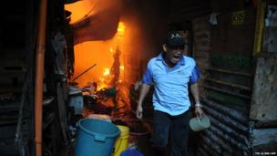 A resident calls out for firefighters as a fire engulfs a shanty town in the financial district of Manila