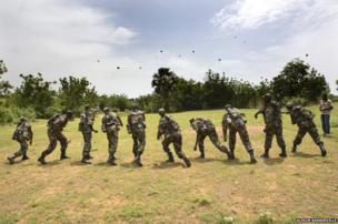The soldiers receive a lesson in how to throw a grenade and practice using rocks