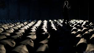 A Bosnian man walks near the 409 coffins of newly identified victims of the 1995 Srebrenica massacre in Potocari Memorial Centre, near Srebrenica