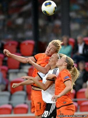 Dutch midfielder Kirsten van de Ven (left) and midfielder Anouk Hoogendijk vie for the ball with Germany's midfielder Lena Goessling
