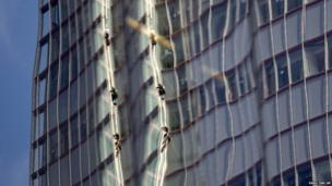 Reflected in a nearby building, Greenpeace protesters climb up The Shard in London, the tallest building in western Europe