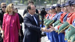 French President Francois Hollande shakes hands next to his partner Valerie Trierweiler.