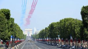 Nine planes from the French Air Force Patrouille de France release trails of red, white and blue smoke, the colours of French national flag as they take part in a fly over during the Bastille Day parade on the Champs-Elysees avenue.
