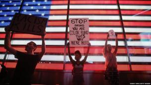 Trayvon Martin supporters stand in front of a lighted American flag in Times Square