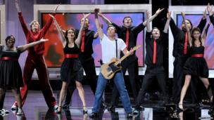 Cory Monteith (back row, centre) and cast of Glee, perform alongside Jimmy Fallon and Tina Fey at the Emmy Awards ceremony in 2010