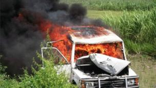 A police vehicle on fire in a field in the Saran district of Bihar state on 17 July 2013