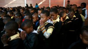 Pupils at the Denver primary school in Johannesburg pray for Nelson Mandela (18 July)