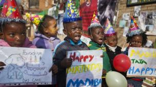Children in party hats with colourful balloons celebrating Nelson Mandela's birthday.