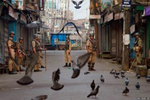 Indian paramilitary soldiers stand guard at a closed market area during curfew in Srinagar, India