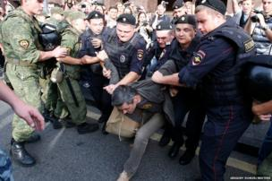 Policemen detain a man during a protest against the sentencing of Russian opposition leader Alexei Navalny