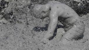 Tourist covered in mud at a festival
