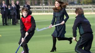 The Duchess of Cambridge plays hockey during a visit to her former preparatory school St Andrew's