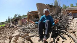 A resident cries on her collapsed house in Hetuo township in China's north-west Gansu province following two earthquakes on 22 July, 2013.