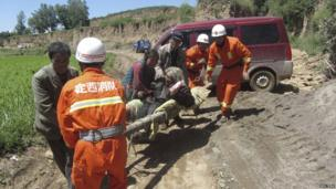 Firefighters carry an injured person along a dirt track on a stretcher after an earthquake hit Minxian county in China's north-west Gansu province on 22 July, 2013.