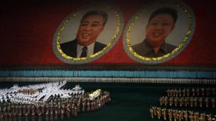 Performers dance in front of portraits of late North Korean leaders Kim Il-sung, left, and Kim Jong-il, right, in Pyongyang, 22 July 2013