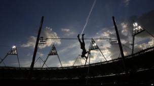 German pole-vaulter Silke Spiegelburg silhouetted against the dusk sky