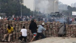 Morsi supporters throw stones from behind a makeshift barricade in Nasr City (27 July 2013)