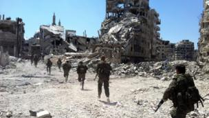 Syrian government forces patrol in the Khalidiyah neighbourhood of the central city of Homs