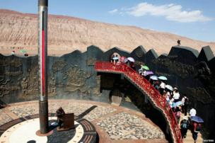 Chinese tourists walk past a huge thermometer near the Flaming Mountain in Turpan