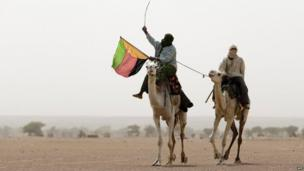 Tuareg man holds the flag of the National Movement for the Liberation of Azawad in Kidal, northern Mali, on 28 July 2013