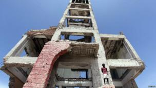 A boy stands on the ruins of the former Somali parliament building in Mogadishu on 1 August 2013