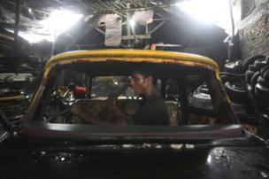 A worker dismantles a Mumbai Premier Padmini taxi in a scrap yard in Mumbai.