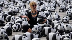 A woman poses as she has her picture taken amid 1600 panda bear sculptures in Berlin