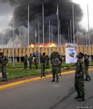 Armed policemen cordon off the area as fire rages at the international arrivals unit of Jomo Kenyatta International Airport, Nairobi, Kenya