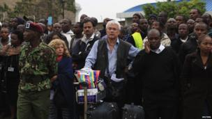 Stranded passengers and onlookers crowd together after a fire disrupted all operations at the Jomo Kenyatta International Airport in Kenya's capital Nairobi 7 August 2013.