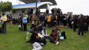 """Stranded passengers and onlookers gather after a fire disrupted all operations at the Jomo Kenyatta International Airport in Kenya""""s capital Nairobi 7 August 2013."""