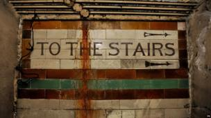 "A view of a ""to the stairs"" sign inside the former Brompton Road tube station."