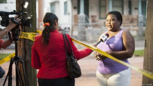 An unidentified woman speaks to a reporter outside the home of Ariel Castro on August 7, 2013 in Cleveland, Ohio